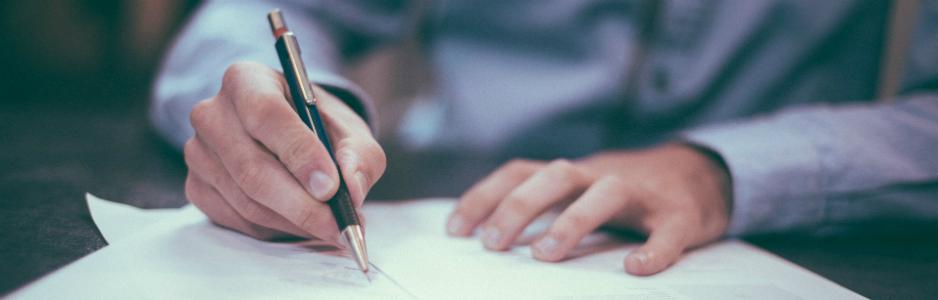 personne écrivant à l'aide d'un stylo à bille